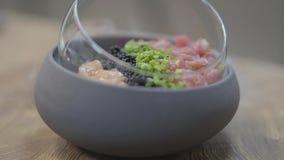 Cloe-up изумляя вкусное блюдо с тунцом, частями семг, ежевиками, зелеными цветами и сухим льдом акции видеоматериалы