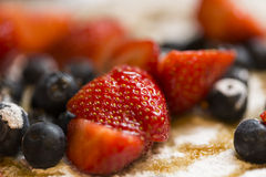 Close up of strawberries and blueberries on a pancake covered in icing sugar and maple syrup Royalty Free Stock Photos