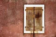 Cloesed iron window with white border. Rusty closed iron window with white border made of sotne. Wall has nice read texture Stock Image