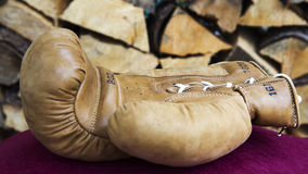 Cloesup of boxing glove in front of firewood royalty free stock photography