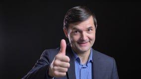 Cloesup krótkopęd dorosły atrakcyjny caucasian mężczyzna pokazuje kciuk w górę i ono uśmiecha się radośnie przed kamerą z zbiory