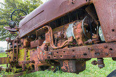 Closeup of the engine of an old abandoned tractor. In a grassy field.  Raining Stock Images