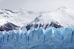 Cloeup of Glacier with Mountains in Background. Closeup of blue glacier with cold, snowy mountains in background royalty free stock images