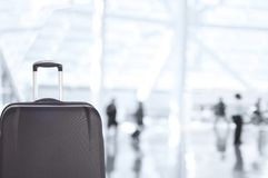 Luggage Closeup with Blurred Travelers in Airport Concourse royalty free stock image