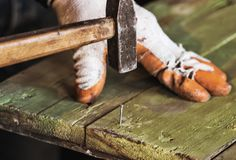 Clogging a nail in a wooden board. Worker in gloves holding and clogging a nail in a wooden board Stock Photography
