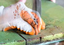 Clogging a nail in a wooden board. Worker in gloves holding and clogging a nail in a wooden board Stock Photo