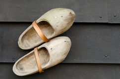 Clogs. Pair of traditional Dutch yellow wooden shoes on a wooden black table Stock Photo