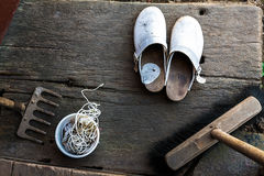 Clogs shoes boots broom string rake wooden porch schoes Stock Photo