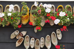 Clogs - shoes on a wooden wall. Royalty Free Stock Photo