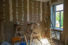 Cloison sèche sur les murs et l'équipement fonctionnant pendant la réparation de la salle photographie stock