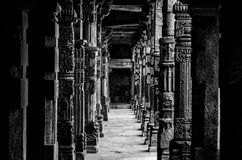 Cloister Columns at Qutb Complex black & white. Cloister columns in black and white with intricate stone carvings at Quwwat ul-Islam Mosque, Qutb complex Royalty Free Stock Photo