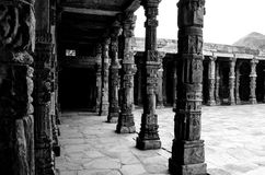 Cloister Columns at Qutb Complex. A different view of cloister columns in black and white with intricate stone carvings at Quwwat ul-Islam Mosque, Qutb complex Royalty Free Stock Photo