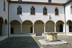 Cloister of the convent with the ancient well. Of rainwater in Italy stock images