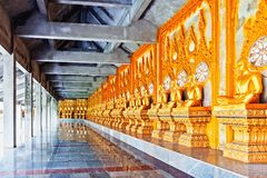 A cloister of Phra Maha Chedi Chai Mongkol lined by row of Buddhist monk statues in Roi Et province, northeastern Thailand Royalty Free Stock Photography