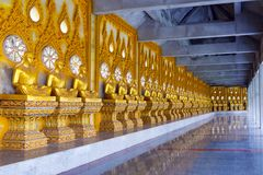 A cloister of Phra Maha Chedi Chai Mongkol lined by row of Buddhist monk statues in Roi Et province, northeastern Thailand Royalty Free Stock Image