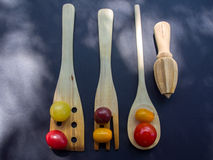 Clolrful Tomatoes and Wooden Instrument. On tha black table Stock Image