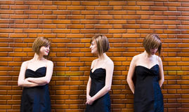 Cloned woman in different expressions. Over brickwall Stock Photo