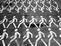 Clones. Many white man figures on black asfalt. Royalty Free Stock Photo