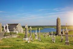 Clonmacnoise domkyrka med de typiska korsen och gravarna fotografering för bildbyråer