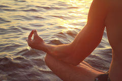 Clope up on male hands meditating in yoga position on the beach near the sea at sunset Stock Photography