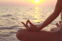 Clope up on women hands meditating in yoga position on the beach Stock Image