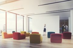 Clored armchairs office classroom, woman, corner. Woman in a corner of an office classroom interior with a number of multicolored armchairs and a white blank Stock Image