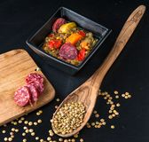 Clorful lentils soup with chorrizo - traditional Spanish cuisine. Colorful lentil soup in a black ceramic bowl, a woden spoon  wth lentil seeds, a wooden board Royalty Free Stock Images