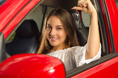 Clos up of a beautiful sexy young woman in red car holding keys and smiling Stock Image
