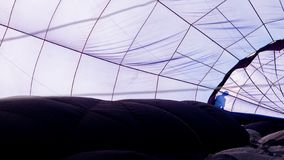 Clos-up of the inside of a blue hot air balloon with the silhouette of a man stock photo