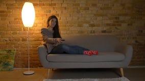 Closdeup fors av den unga gulliga caucasian kvinnlign som vilar på soffan och rymmer en avlägsen TVkontroll som chockas och fotografering för bildbyråer