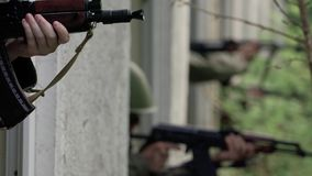 Close – Soldiers aim target out of window stock footage