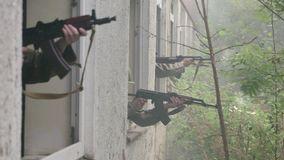 Close – Soldiers aim target out of window stock video footage