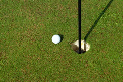 So close 2. White golf ball near hole on green stock image