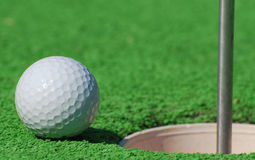 So Close!. A close up of a gold ball near the cup on the green royalty free stock image