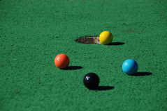 So Close!. Four putt-putt golf balls, near the hole Royalty Free Stock Photos
