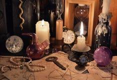 03_Close acima de objetos e de velas mágicos na tabela da bruxa Imagem de Stock