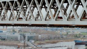 Close aerial shot of big modern truck crane located at truss bridge at the background of cityscape. Close aerial shot of big modern truck crane located at truss stock footage