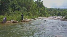 Close Arial View Fishermen Walk along River Bank in Tropics stock video footage