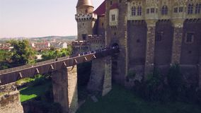 Close aerial view of a medieval castle with bridge surrounded by green park stock footage