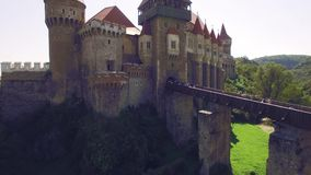 Close aerial view of a medieval castle with bridge surrounded by green park stock video