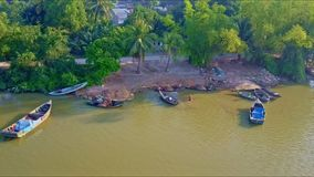 Close Aerial View River Bank with Motor Boats and Road. Close aerial view of ground river bank with wooden motor fishing boats by road with small traffic behind stock video