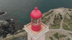 Close ascending aerial shot of lighthouse on the coast above the ocean with the city in the background in Catalonia stock footage