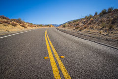 Close Asphalt Bend in Road. Lines of the road wind through barren south west desert in the United States stock photos