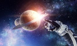 Touching the uniqueness. Mixed media. Close of astronaut robotic hand touching planet. Elements of this image furnished by NASA Royalty Free Stock Photography