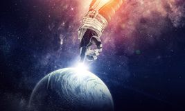 Touching the uniqueness. Mixed media. Close of astronaut robotic hand touching planet. Elements of this image furnished by NASA Stock Photography