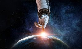 Touching the uniqueness. Mixed media. Close of astronaut robotic hand touching planet. Elements of this image furnished by NASA Stock Photo