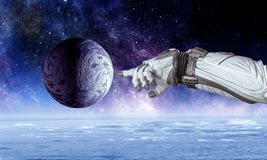 Touching the uniqueness. Mixed media. Close of astronaut robotic hand touching planet. Elements of this image furnished by NASA Royalty Free Stock Photos