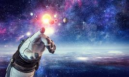 Touching the uniqueness. Mixed media. Close of astronaut robotic hand touching planet. Elements of this image furnished by NASA Royalty Free Stock Photo