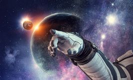 Touching the uniqueness. Mixed media. Close of astronaut robotic hand touching planet. Elements of this image furnished by NASA Royalty Free Stock Image