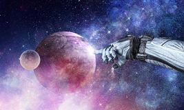 Touching the uniqueness. Mixed media. Close of astronaut robotic hand touching planet. Elements of this image furnished by NASA Stock Image